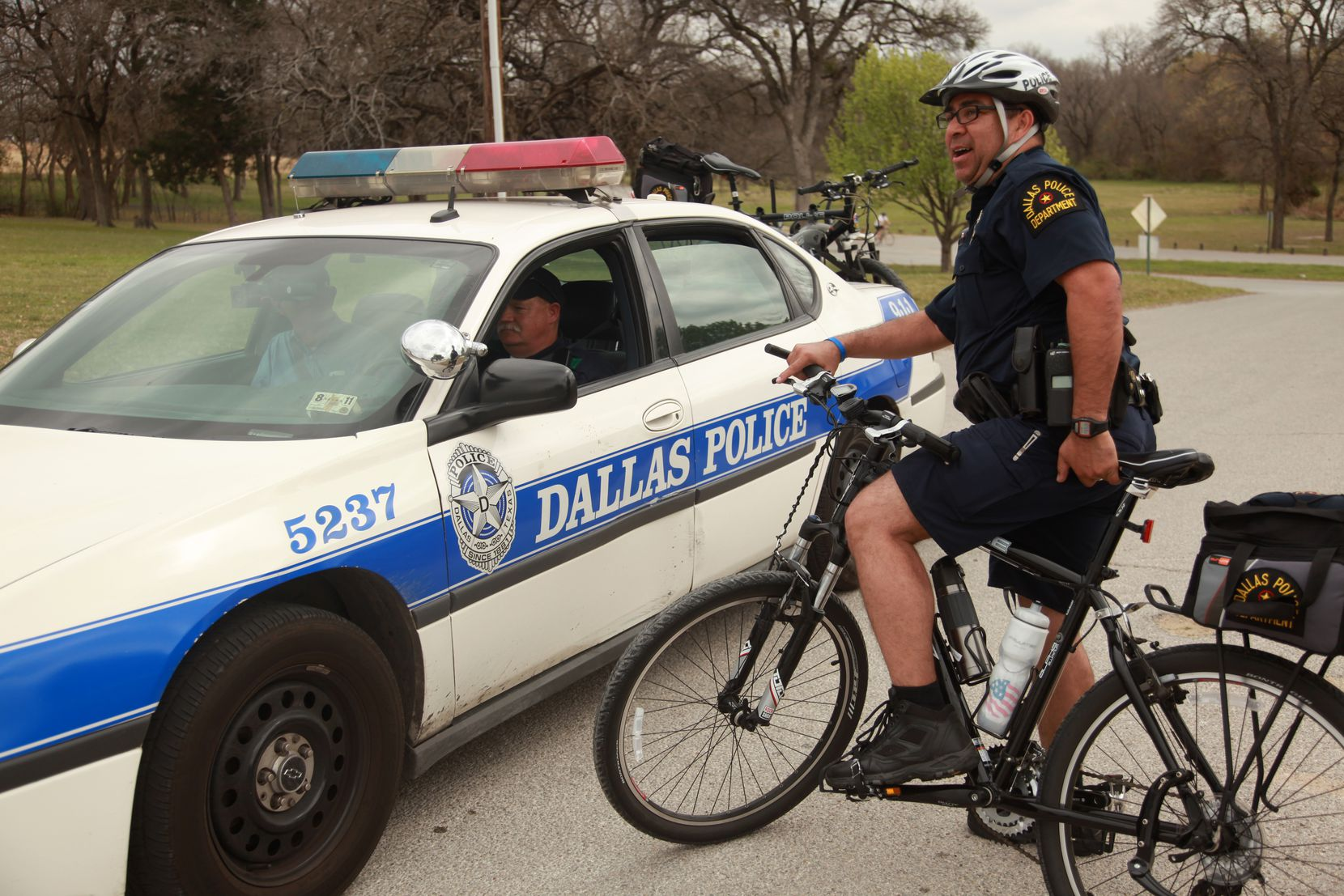 Dallas police officers Juan Amaya (on bike) and Scot Jenkins talked during a patrol  around White Rock Lake in March 2011.