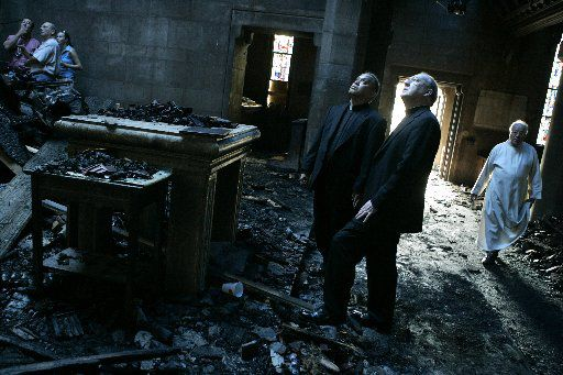 Edmundo Paredes (center left) and then-Dallas Bishop Kevin Farrell (center right) surveyed the damage after a five-alarm fire destroyed St. Cecilia's Catholic Church in Oak Cliff in August 2007.