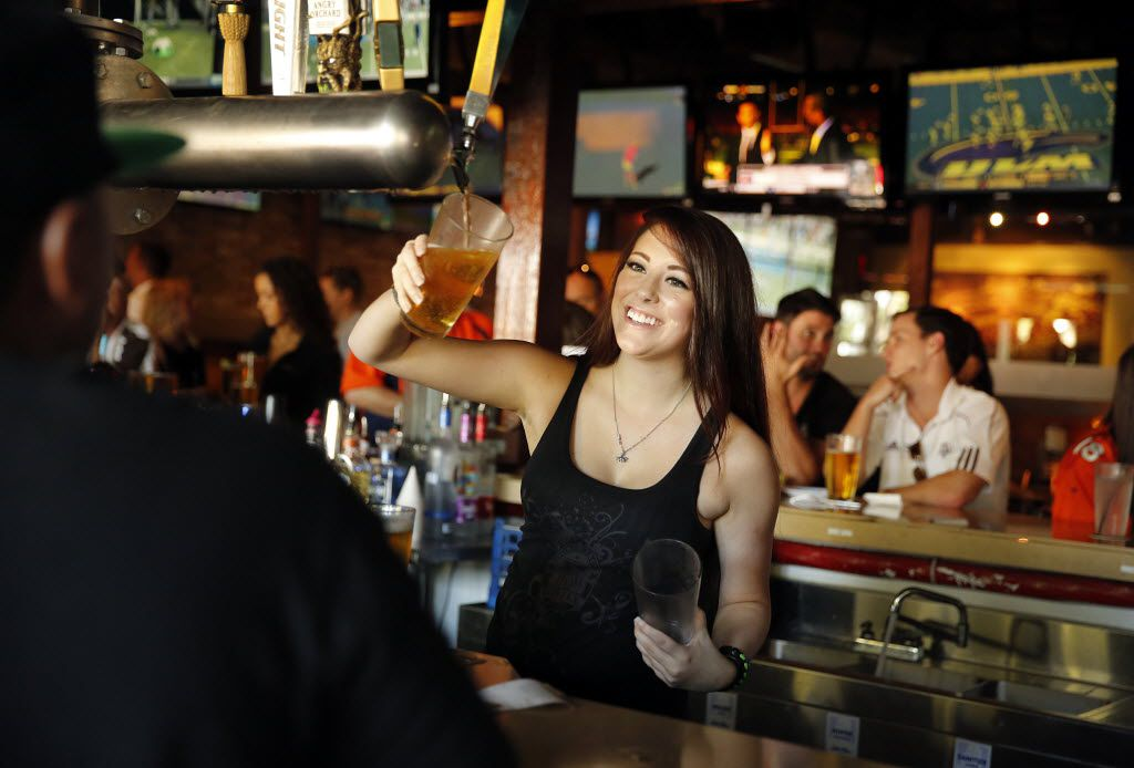 Boomerjack's Grill and Bar server Keigan Smith visits with patrons at their North Arlington, Texas location while serves up cold beers. The city's restaurants and bars reported more than $14 million in alcohol sales in May, up 175% since the state fully reopened.