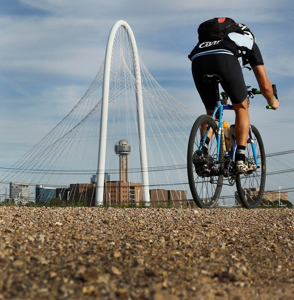 A cyclist makes his way along a path on the levee off of Canada Drive in West Dallas.