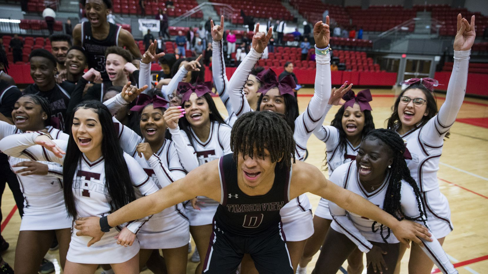 Mansfield Timberview guard Joey Madimba, cheerleaders and other players celebrate a 40-36 win over Denton Braswell in Thursday's Class 5A area-round playoff game at Coppell High School.