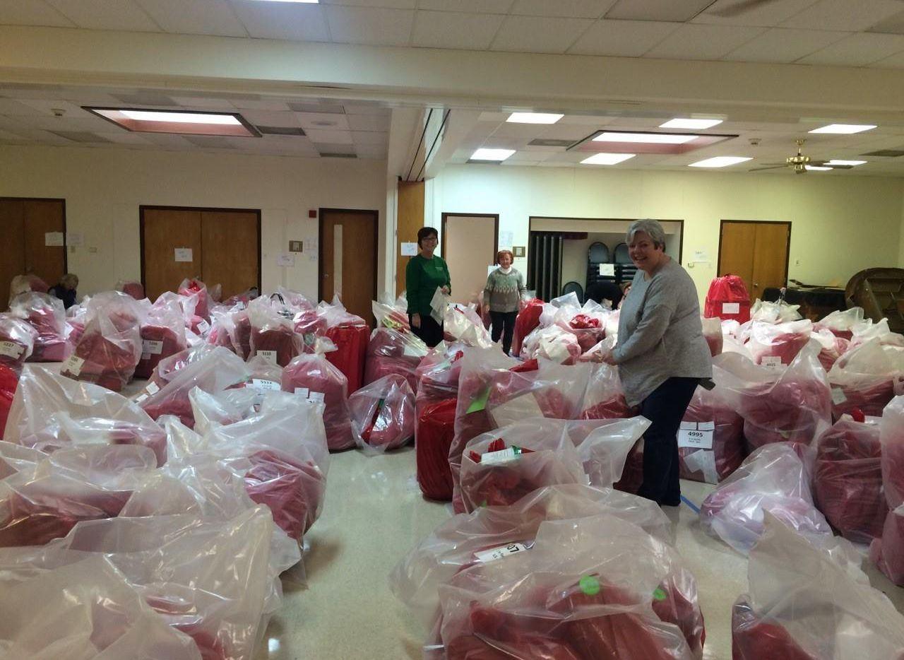 Representantes de Angels of Charity Women's Auxiliary preparan las bolsas con regalos para las familias de West Dallas.(CORTESÍA)