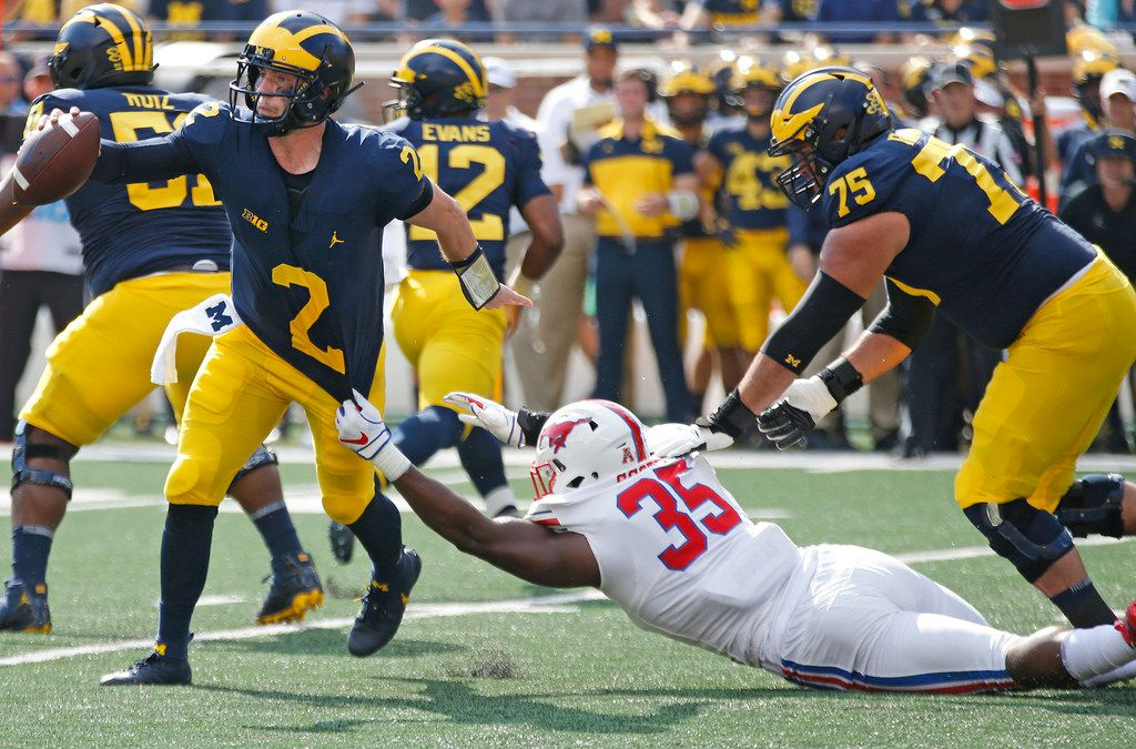 Southern Methodist Mustangs defensive end Delontae Scott (35) tries to hang on to Michigan Wolverines quarterback Shea Patterson (2) in the first quarter during the SMU Mustangs vs. the Michigan Wolverines NCAA football game at Michigan Stadium in Ann Arbor, Michigan on Saturday, September 15, 2018.