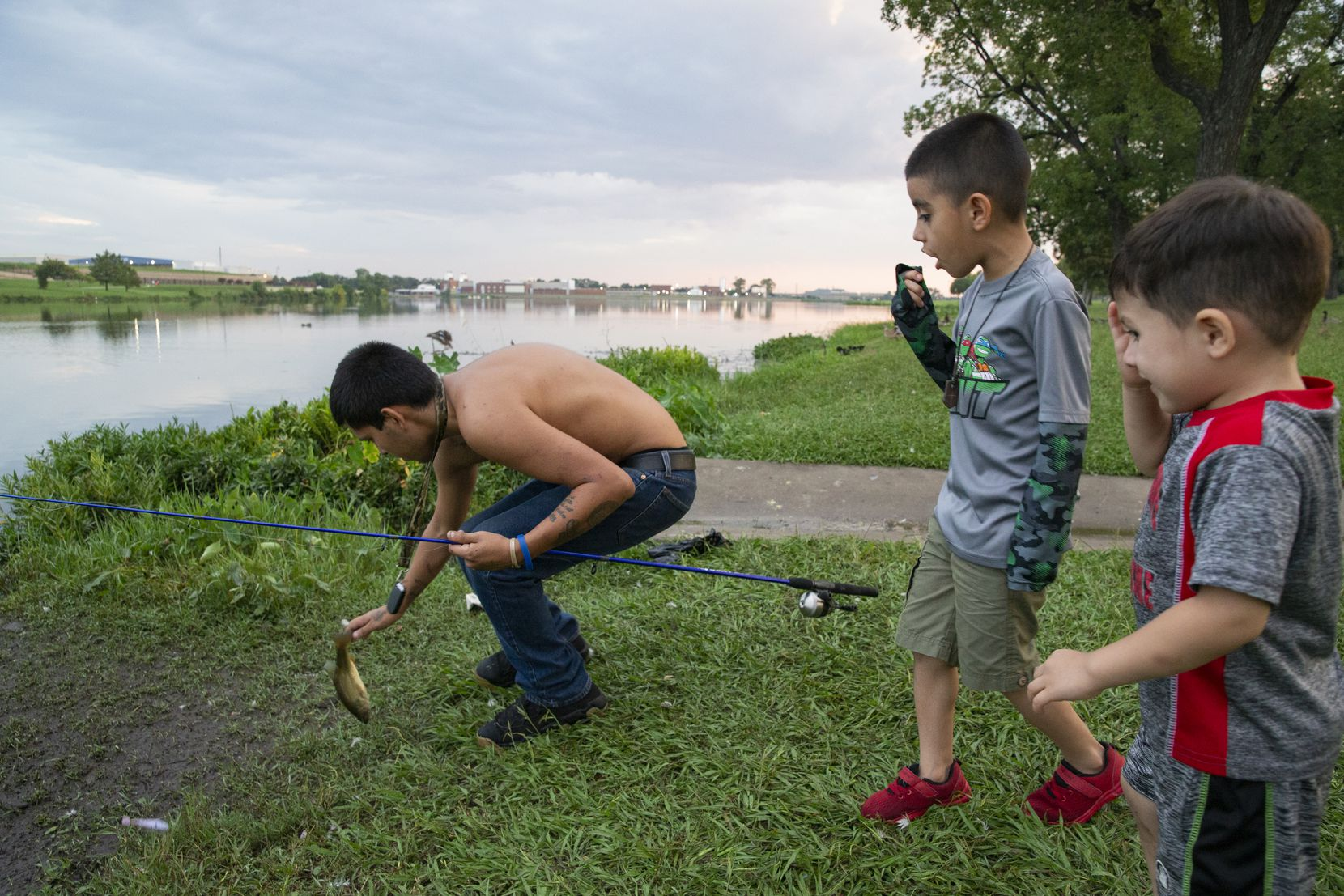 Terrance Hunt gets ready to throw a fish back as Milton Smith Ceren Mejía, 7, and Edrick Gael Mejía, 2, watch on the northern side of Bachman Lake Park.