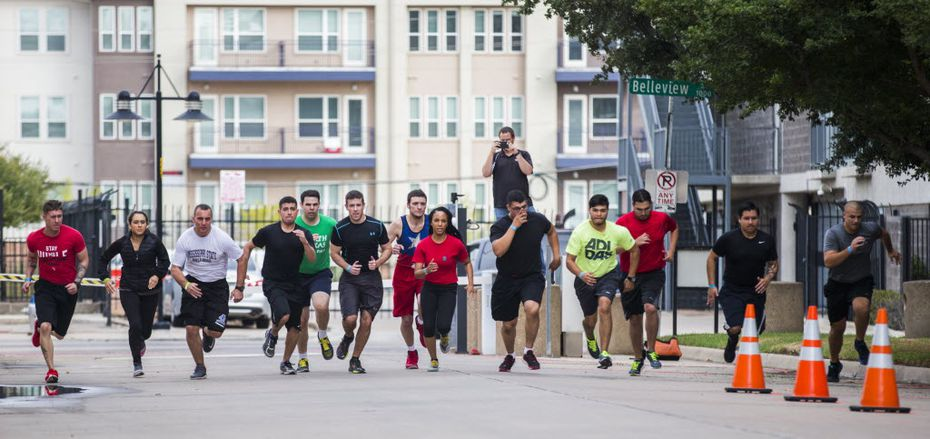 Dallas police candidates ran a 300-meter time trial while undergoing physical tests.   (Ashley Landis/Staff Photographer)