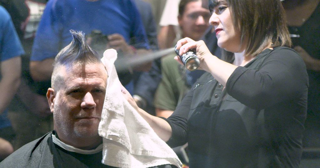 Stylist Vicky Peña sprays temporary hair dye on George Dunham's hair at Boardroom Salon for Men at Inwood Village in Dallas on Sept. 6, 2019. The Ticket host lost a bet saying Cowboys' coach Jason Garrett would be fired by the end of last season. The radio host must now sport a mohawk for the entire upcoming Cowboys season. (Tommy Noel/Staff Photographer)