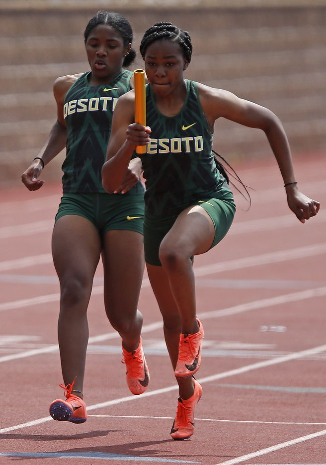 Mia Abraham (left) hands off to Trinity Kirk as they compete for DeSotto High School in the girls 4x200 during the Jesuit-Sheaner Relays held at Jesuit College Preparatory School in Dallas on Saturday, March 27, 2021.  (Stewart F. House/Special Contributor)