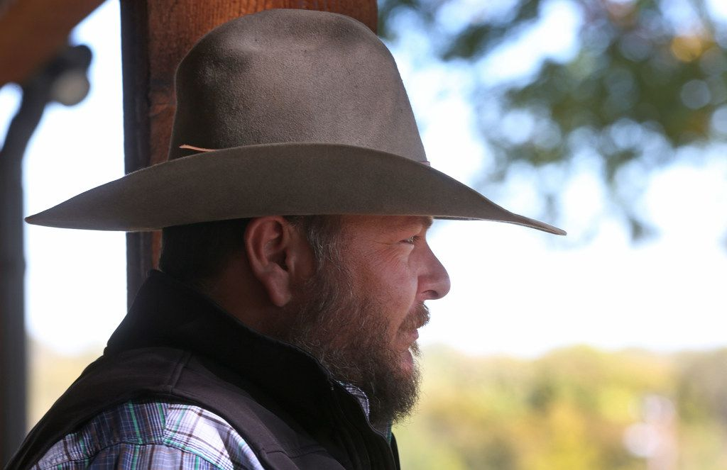 Cade Nichols of A Bar N Ranch stands on the porch at the ranch in Sherman.