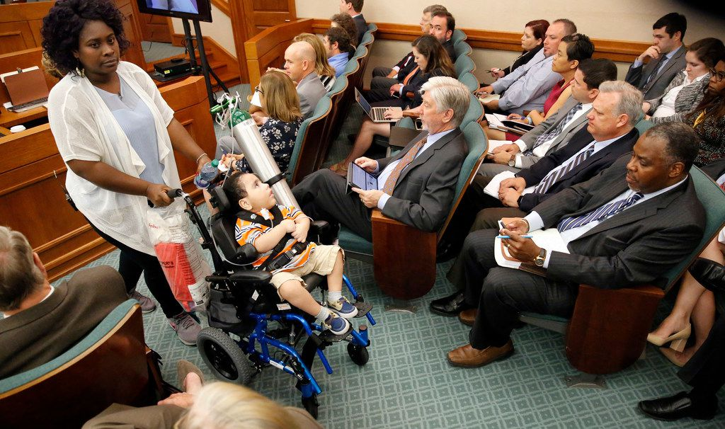 Linda Badawo (left) of Mesquite pushes her medically fragile son, D'ashon Morris, past representatives of Superior HealthPlan, seated right, after testifying before the Texas House Committee General Investigating and Ethics at the Texas Capitol in Austin, in June.