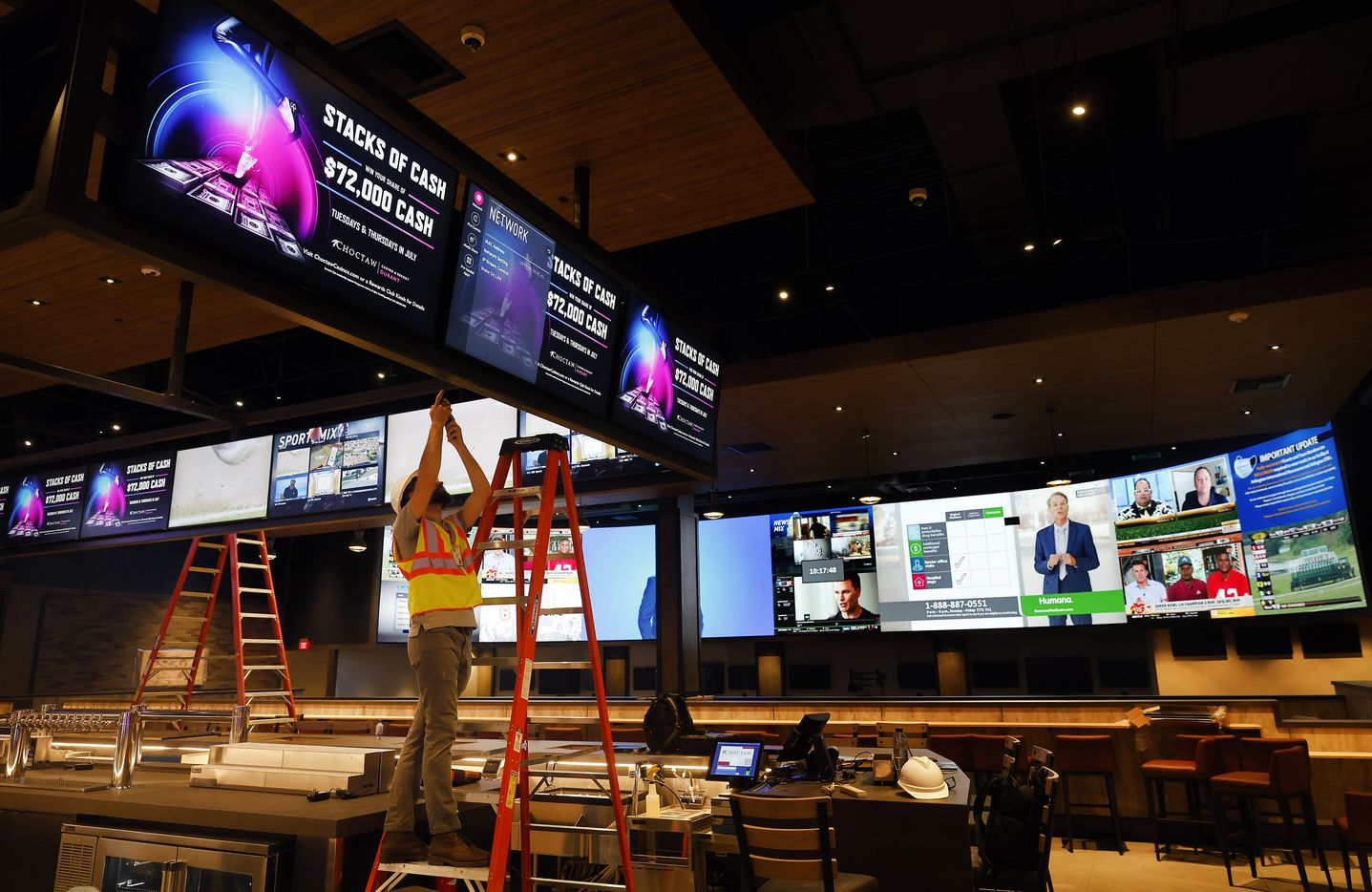 A worker puts the finishing touches on a bank of video screens hanging over The League casino sports bar.