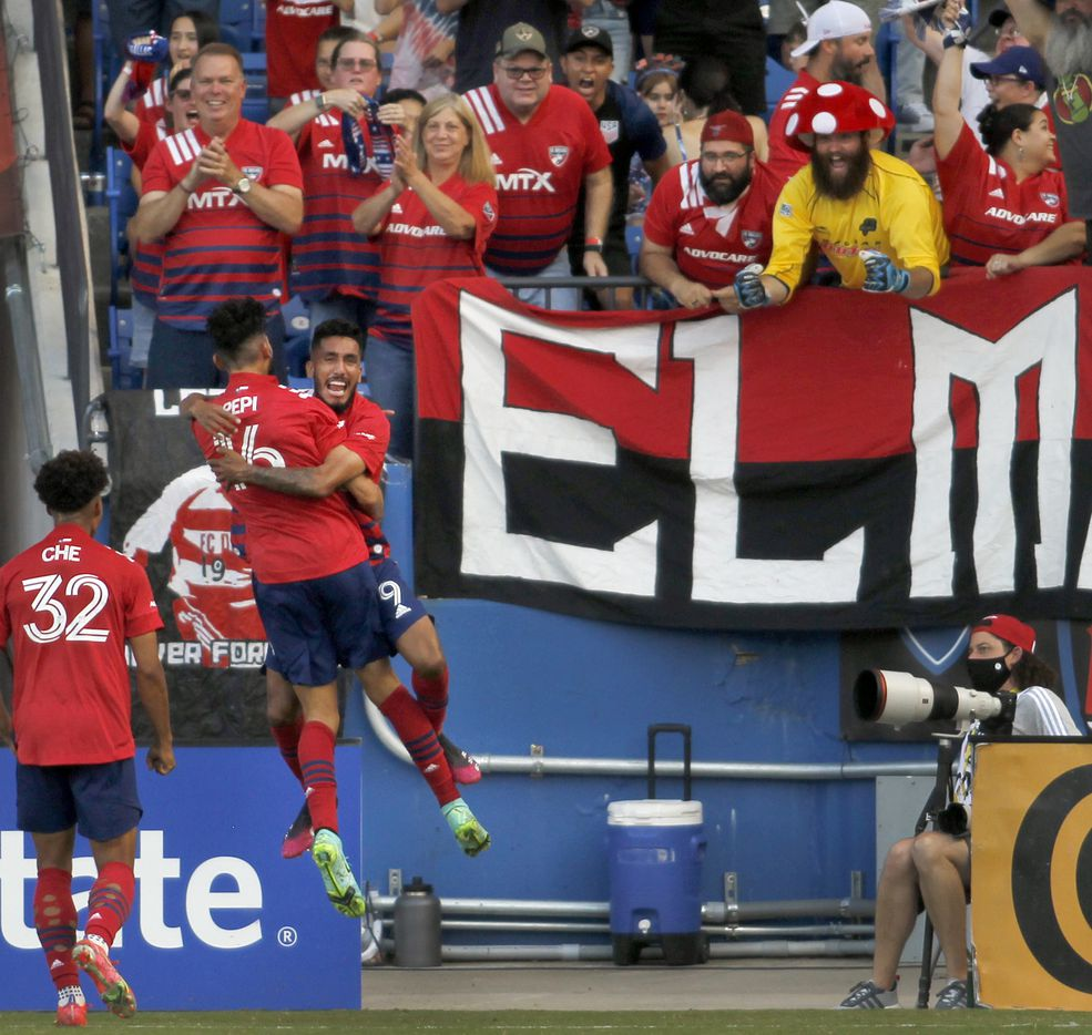 FC Dallas forward Ricardo Pepi (16) back to camera receives a celebratory flying hug from teammate Jesus Ferreira (9) after Pepi's first half goal to break a scoreless tie in their match against Vancouver. The two Major League Soccer teams played their match at Toyota Stadium in Frisco on July 4, 2021.