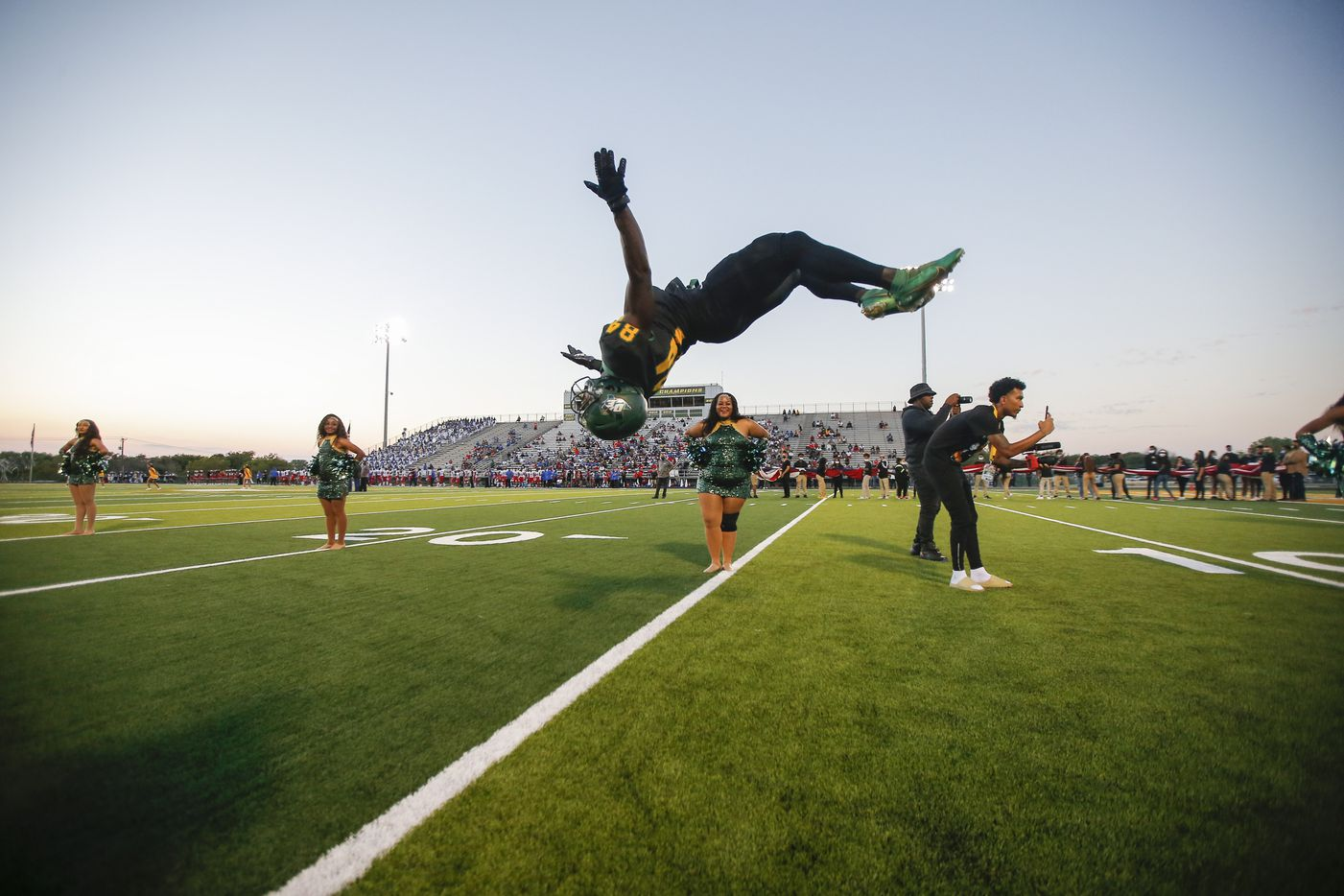 DeSoto senior wide receiver Marquis Wortham (84) does a back flip as he leads his teammates onto the field for the first half of a high school football game against Duncanville at DeSoto High School, Friday, September 17, 2021. (Brandon Wade/Special Contributor)
