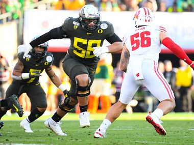 FILE - Oregon offensive tackle Penei Sewell (58) looks to block Wisconsin outside linebacker Zack Baun during the Rose Bowl game on Jan. 1, 2020, at the Rose Bowl in Pasadena, Calif. (Photo by Brian Rothmuller/Icon Sportswire via Getty Images)