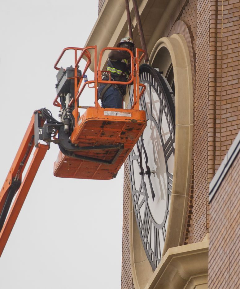 Workers from MEI Rigging & Crating work to install a 12-foot glass clock on the Grapevine Main Station's Observation Tower on Sept. 3, 2020 in Grapevine. (Juan Figueroa/ The Dallas Morning News)