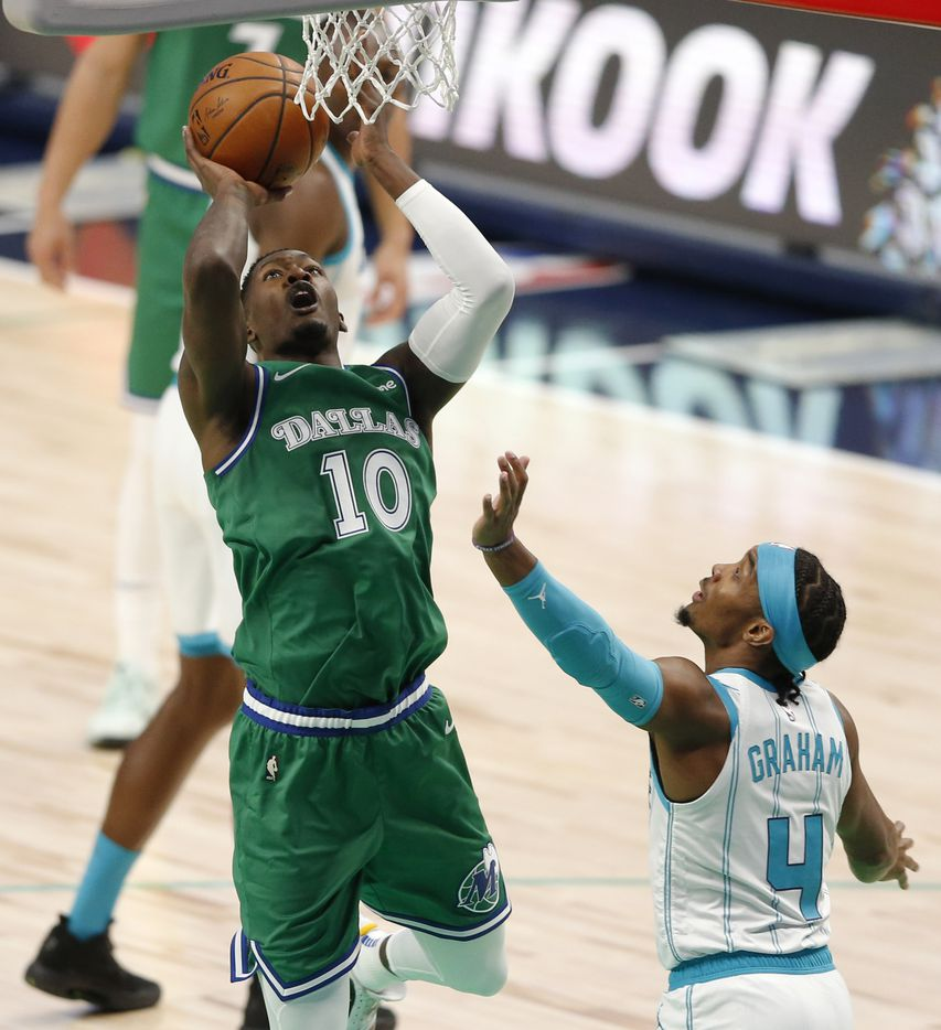 Dallas Mavericks forward Dorian Finney-Smith (10) shoots over Charlotte Hornets guard Devonte' Graham (4) during the first quarter of play in the home opener at American Airlines Center on Wednesday, December 30, 2020 in Dallas. (Vernon Bryant/The Dallas Morning News)