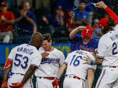 Texas Rangers celebrate after second baseman Brock Holt (16) singles out to centerfield, earning the Rangers a win in the bottom of the eleventh inning against the San Francisco Giants at Globe Life Field in Arlington, Texas, in Dallas on Wednesday, June 9, 2021.