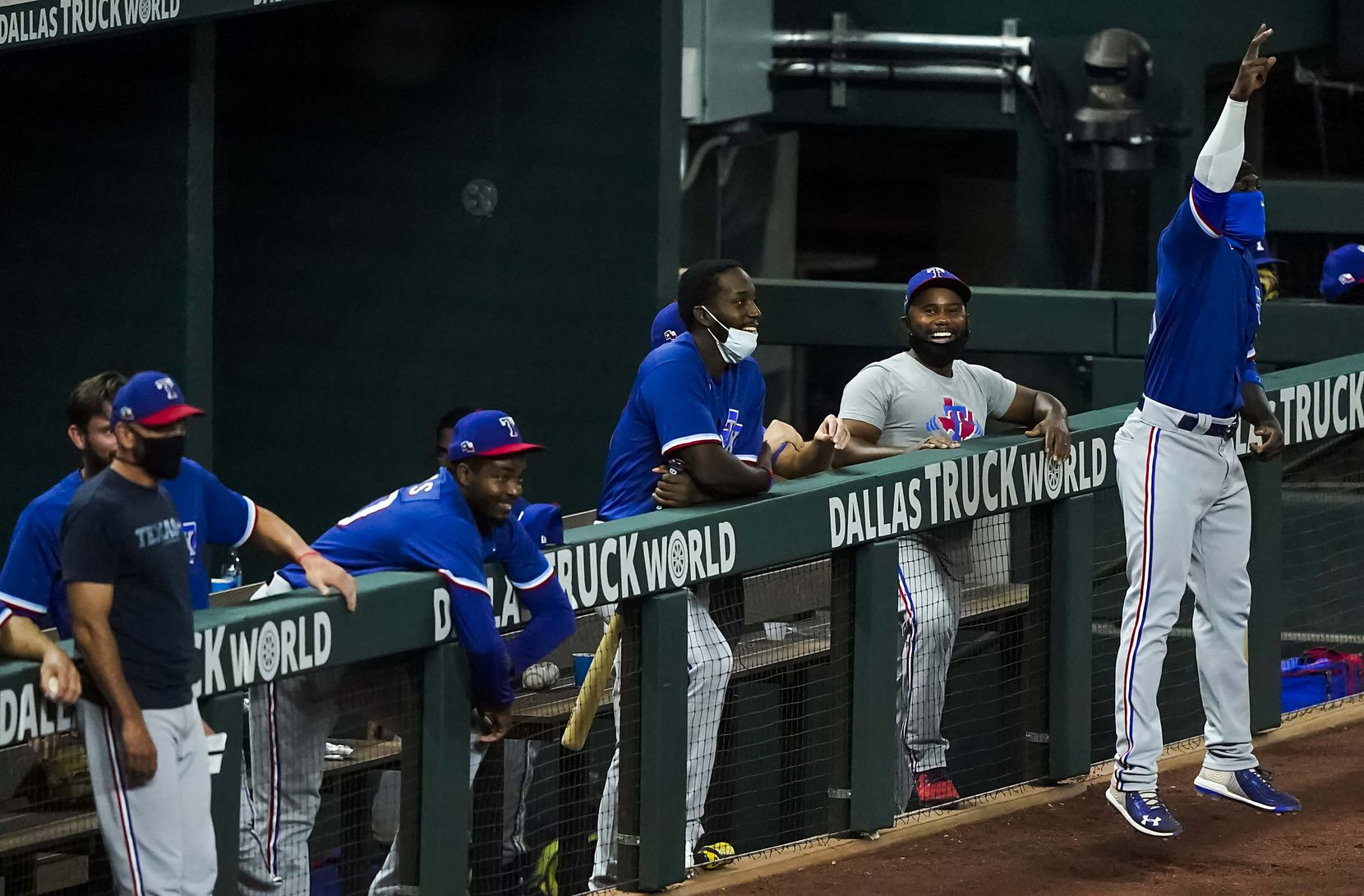 Adolis Garcia (far right) celebrates after Shin-Soo Choo drove in a run with a bunt single during a Texas Rangers Summer Camp intrasquad game at Globe Life Field on Saturday, July 18, 2020.