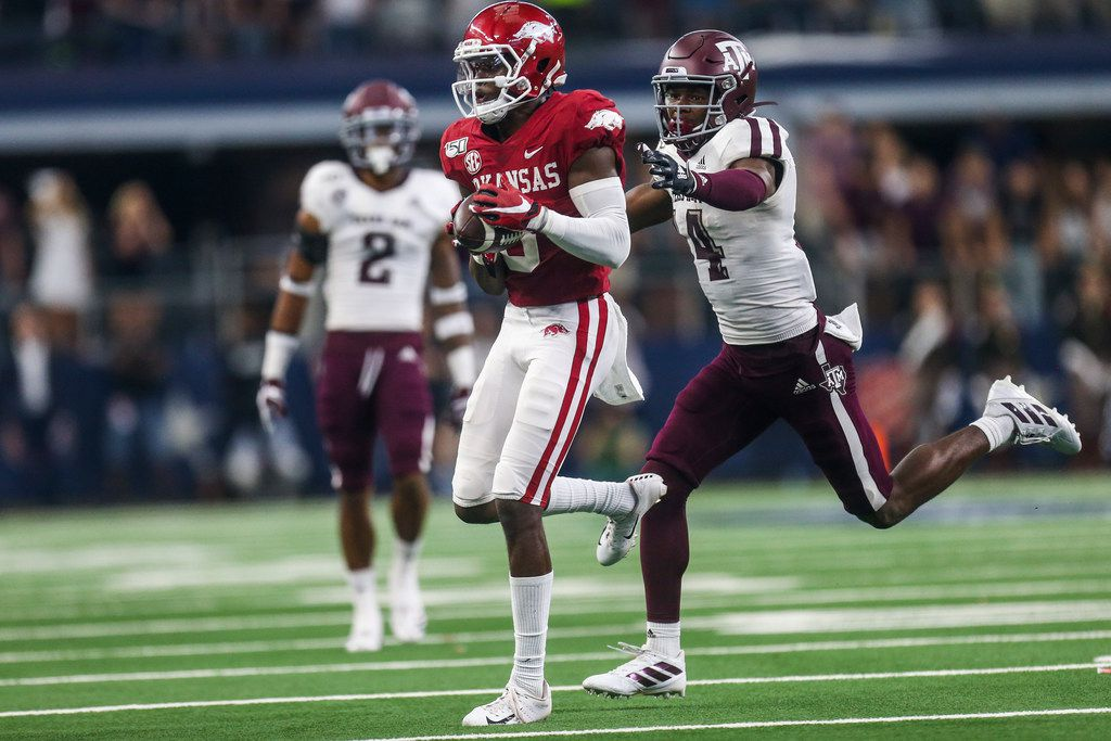Arkansas Razorbacks wide receiver Mike Woods (8) controls the ball as he is defended by Texas A&M Aggies defensive back Keldrick Carper (14) during the second half of a NCAA football game between Texas A&M Aggies and Arkansas Razorbacks on Saturday, September 28, 2019 at AT&T Stadium in Arlington, Texas.