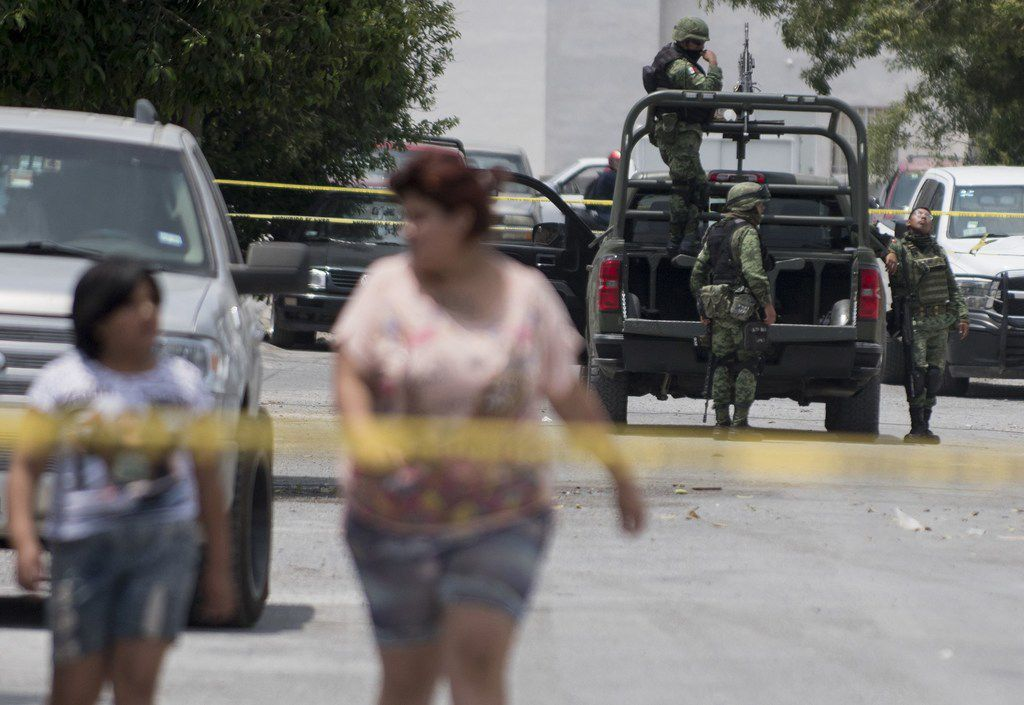 Mexican soldiers stand by at the scene where an armed group confronted the police resulting in nine civilians killed and two policemen wounded in Saltillo, Coahuila state on April 27, 2019.