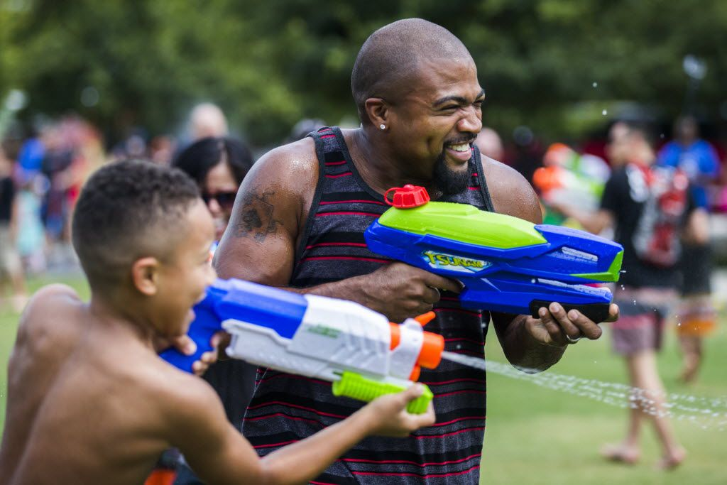 Jaylen Mayo, 8, and his dad, Ahmad Mayo, both of Denton, Texas, participate in a massive water gun fight hosted by Dallas Flash Mob on Saturday, September 5, 2015 at Klyde Warren Park in Dallas. (Ashley Landis/The Dallas Morning News)