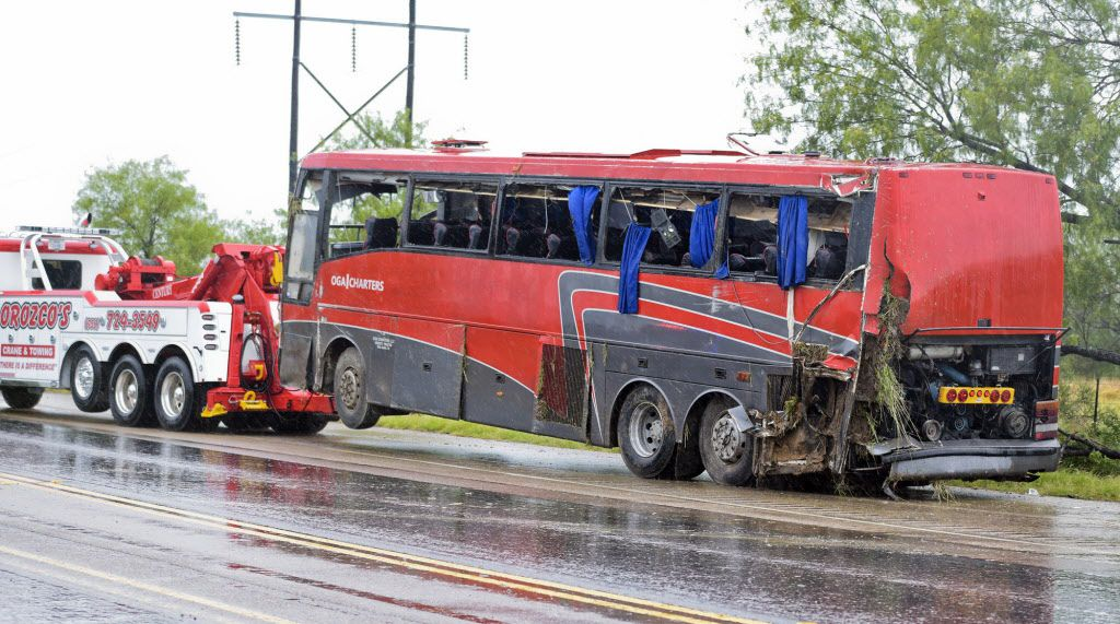 A damaged OGA Charters bus is hauled away after a fatal rollover Saturday on U.S. 83 North in Texas. (Danny Zaragoza/Laredo Morning Times)