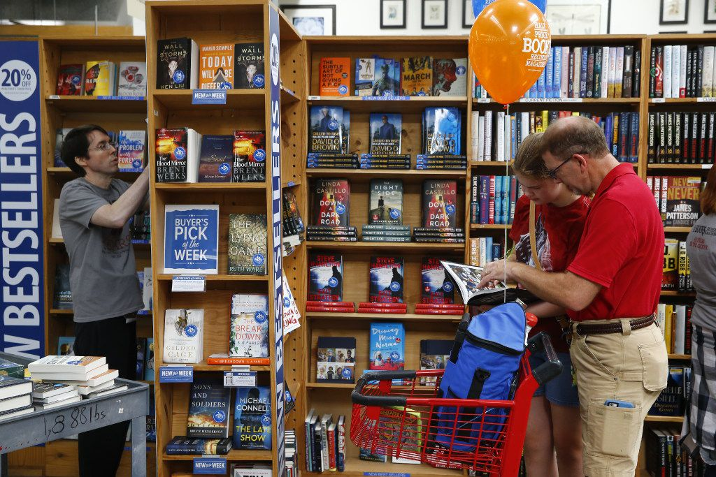 Allen Watson (left) sorts books as Lily Dorris, 13, and her father, Anthony Dorris, browse at Half Price Books'  Northwest Highway flagship store.