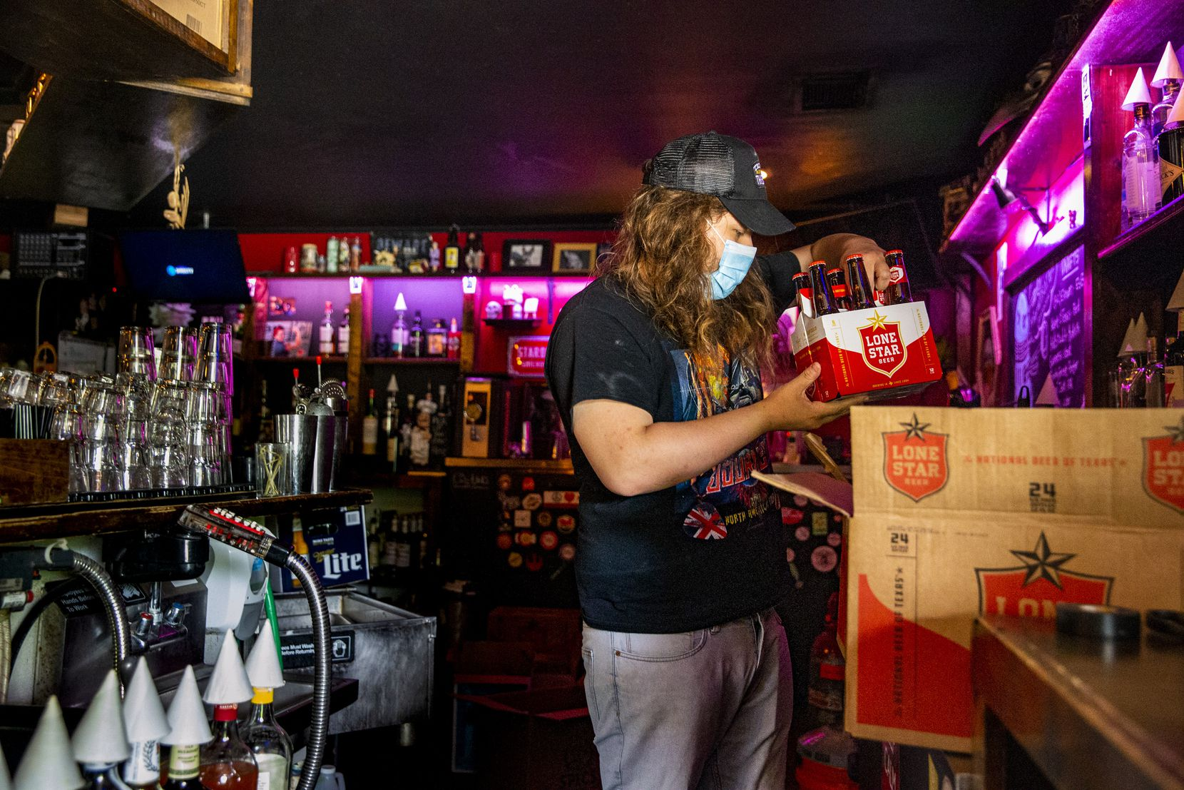 Manager Britt Clardy restocks supplies at Ten Bells Tavern in the Bishop Arts District of Dallas on Thursday, May 21, 2020. Texas Governor Greg Abbott announced on Monday that bars may begin reopening at 25% capacity on Friday.  (Lynda M. Gonzalez/The Dallas Morning News Pool)
