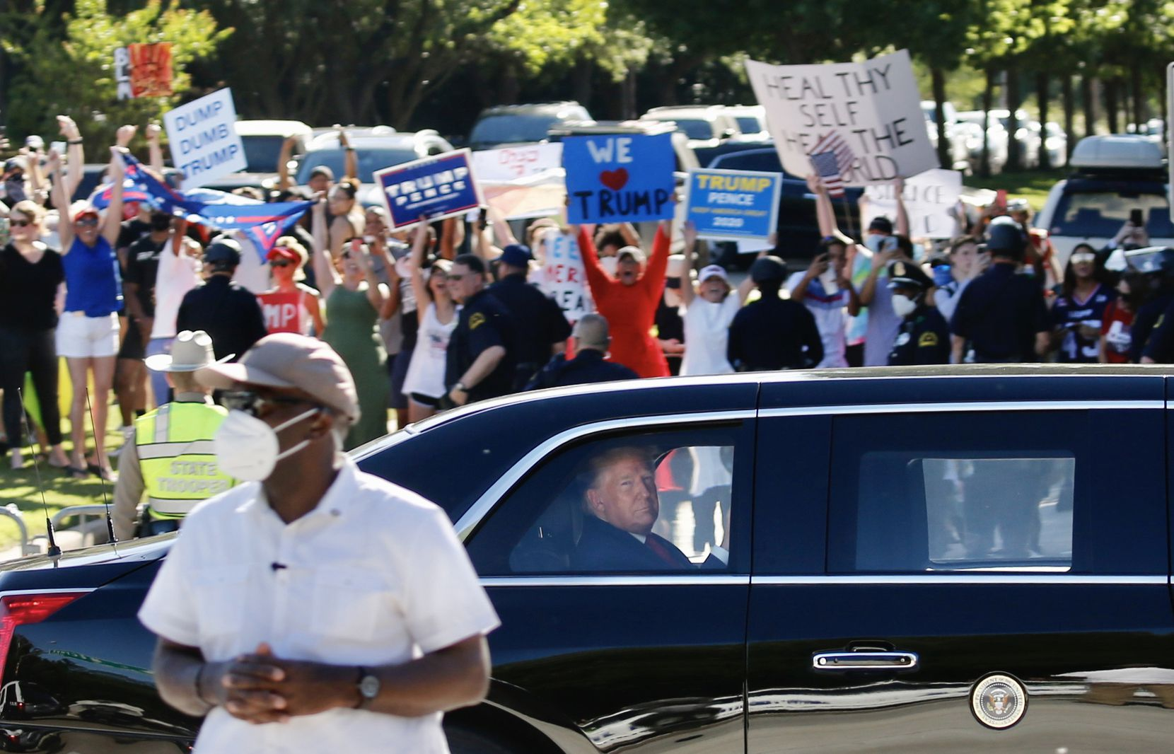 """Supporters and detractors lined the road as President Donald Trump rode in the presidential limo on Hillcrest Road in Dallas after leaving Gateway Church on June 11. Trump attended a discussion at the church about race relations and policing, recommitting to a policy that police """"dominate the streets."""""""