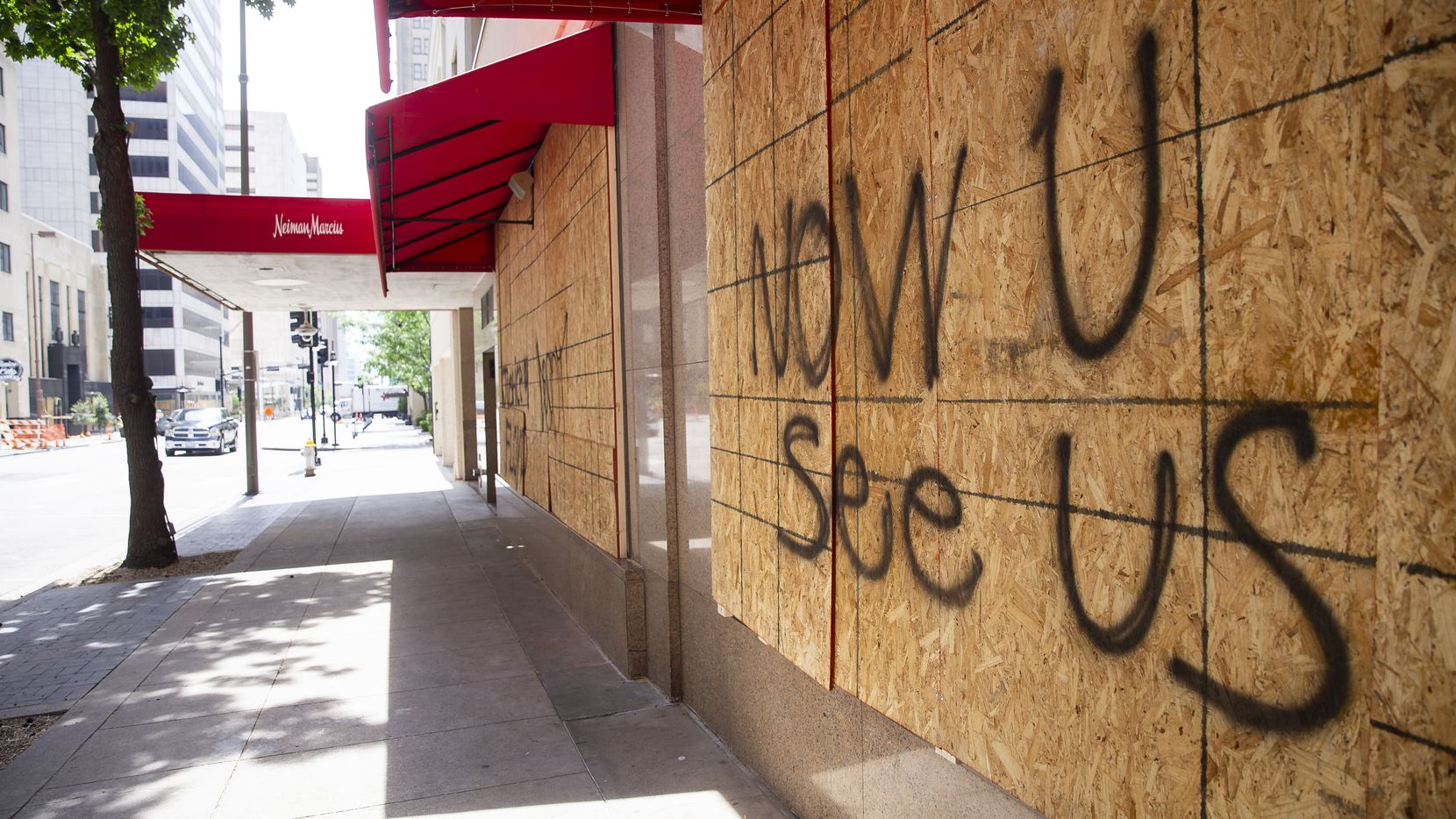 Messages were spray-painted on the boarded-up windows of downtown Dallas' Neiman Marcus on Monday.