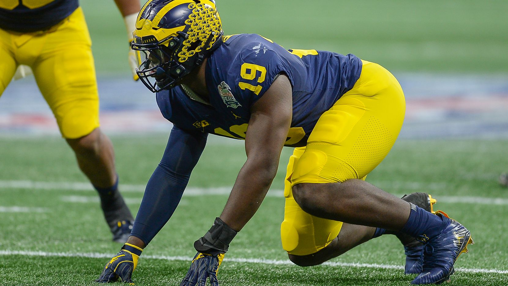 Michigan defensive end Kwity Paye (19) prepares to rush the quarterback during the Peach Bowl against Florida on Dec. 29, 2018, at Mercedes-Benz Stadium in Atlanta. (Photo by Rich von Biberstein/Icon Sportswire via Getty Images)