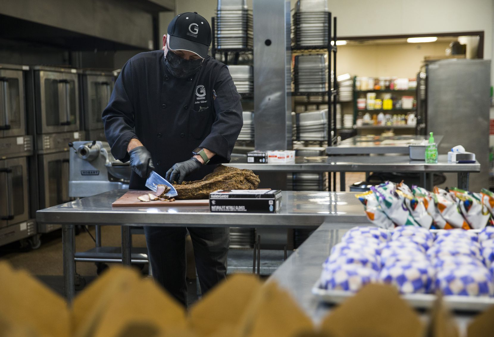 John Gilbert, owner of G-Texas Custom Catering, slices brisket for box lunches for Austin Street Shelter on Saturday, April 11, 2020 at G-Texas Custom Catering in Dallas.