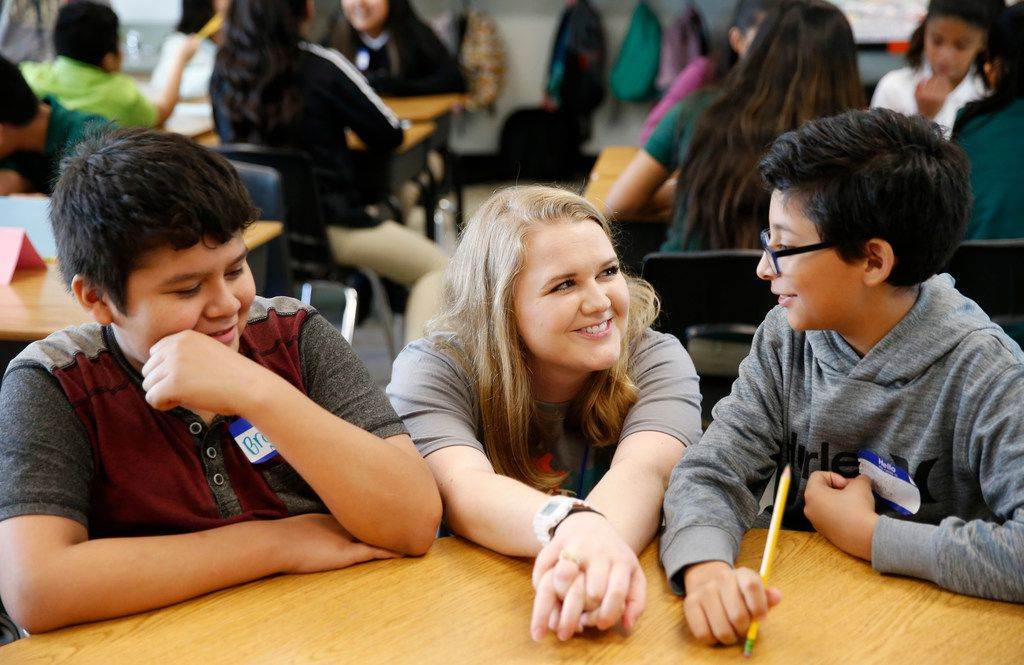 New teacher Caroline Rodgers talks with Brandon Garcia (right) as Brandon Navarr looks on during their sixth-grade class at Carolyn G. Bukhair Elementary School in Dallas on August 20, 2018. Rodgers' grandmother is Carolyn Bukhair, the school's namesake.