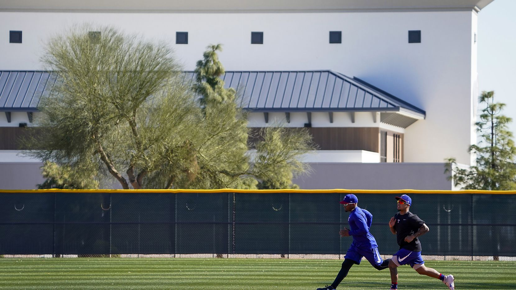 FILE - The new Rangers Village, a housing complex and performance center for minor league players, is pictured in the background as outfielder Willie Calhoun (right) and infielder Andy Ibanez run on a practice field on Thursday, Feb. 13, 2020, in Surprise, Ariz.