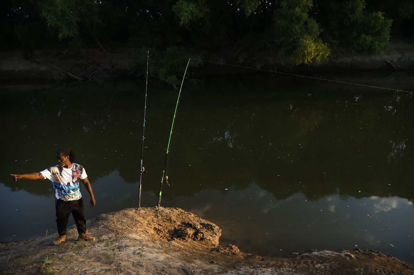 Odell Allen sets his 12 ft rods on the banks of the Trinity River hoping to catch an alligator gar Monday, August 30, 2021.  Texas Parks and Wildlife Department is adding new regulations to limit how many gar each angler can harvest in a year because of overfishing of the native species. (Tom Fox/The Dallas Morning News)