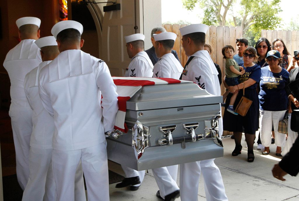A U.S. Navy honor guard carries the body of Gunner's Mate 2nd Class Noe Hernandez into the funeral home as his wife, Dora Martinez Hernandez, holds their son Leon, 3, in Weslaco.