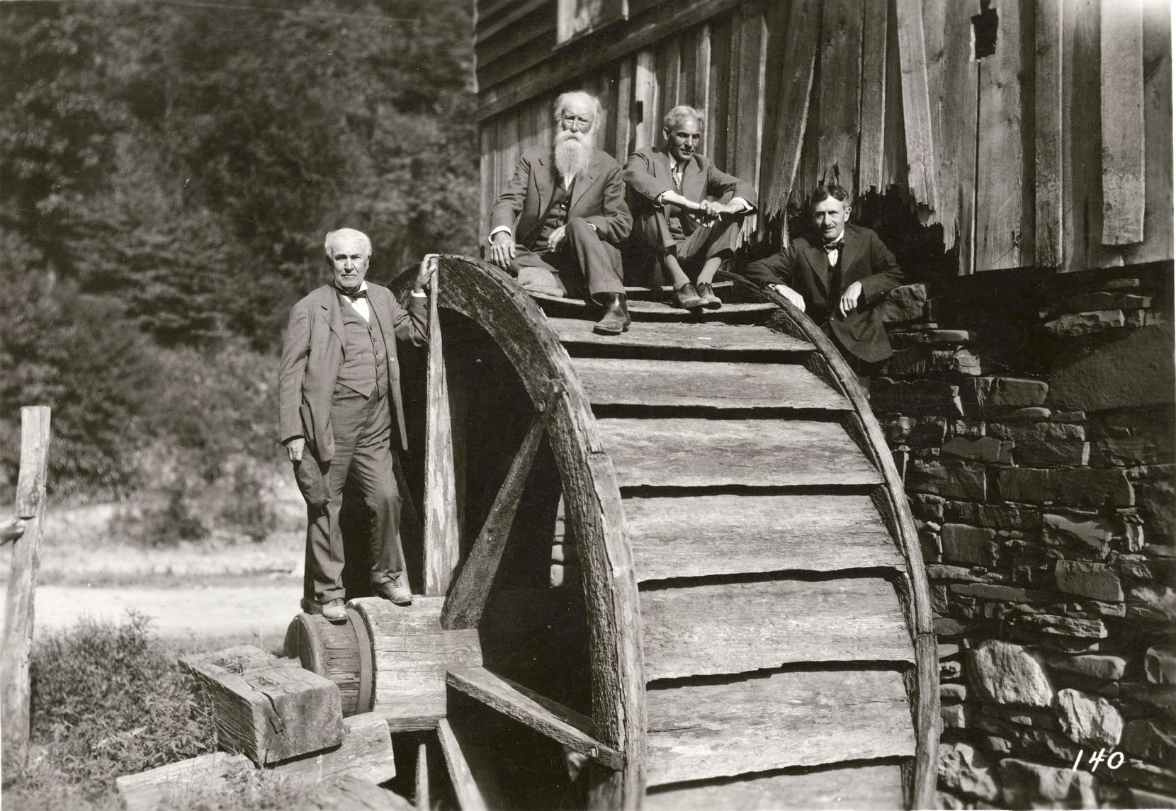 (From left) Thomas Edison, naturalist John Burroughs, Henry Ford and Harvey Firestone pose on a water mill wheel.