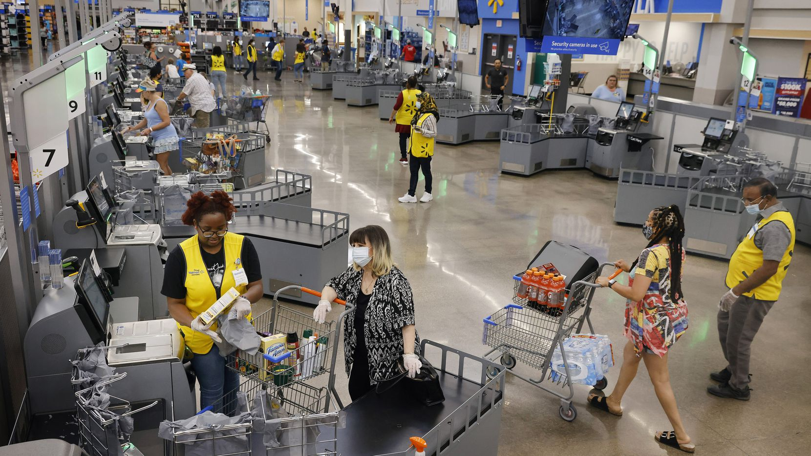 Associates dressed in yellow vests assist customers at the new self checkout corral inside  the Walmart Supercenter on Ohio Drive in Plano, Texas, July 16, 2021. The store is testing a large corral of self checkout stations with a big open space in the middle where the old cashier lanes used to be. (Tom Fox/The Dallas Morning News)