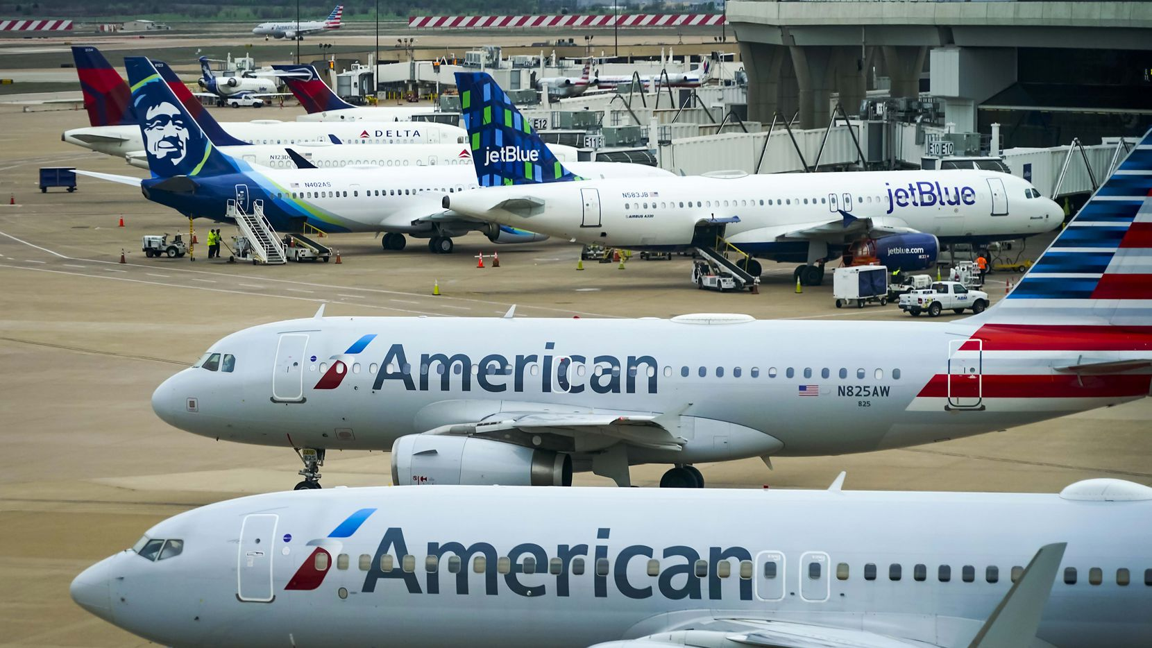 American Airlines planes taxi from gates at DFW International Airport in March 2020.
