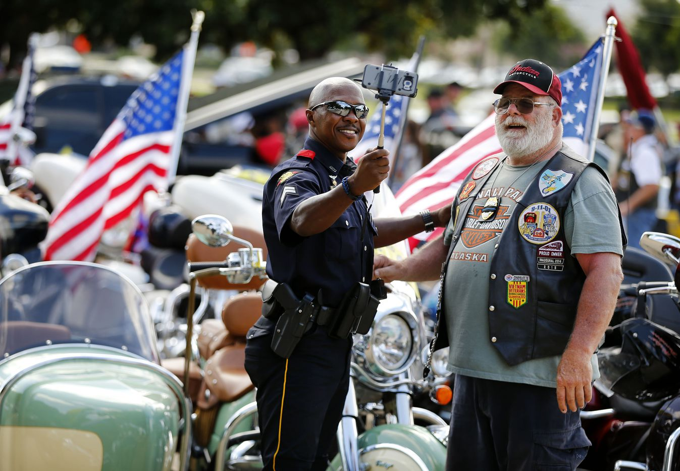 Dallas police Corporal Michael Scott of the motorcycle unit (left) takes a selfie with motorcyclist Mike Delong as they wait for the funeral procession of fallen Dallas police officer Lorne Ahrens at Prestonwood Baptist Church in Plano, Wednesday, July 12, 2016.