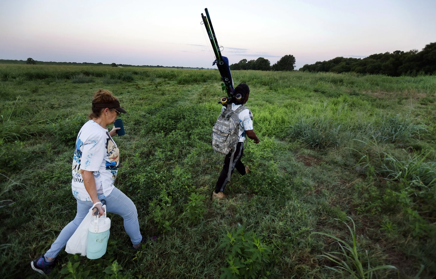 In search for their fishing spot, Odell Allen and his wife Beverly Rasnick hike through high grass and vegetation of the Trinity River bottoms near the Westmoreland bridge, Monday, August 30, 2021. Allen's viral videos of him catching 6-7 foot alligator gar in the Trinity River have made Dallas a popular spot for anglers all over the world who want to hook a gar. It has also led to overfishing of the native species, TPWD says. Texas Parks and Wildlife Department is adding new regulations to limit how many gar each angler can harvest in a year. Allen catches and releases his gars. (Tom Fox/The Dallas Morning News)