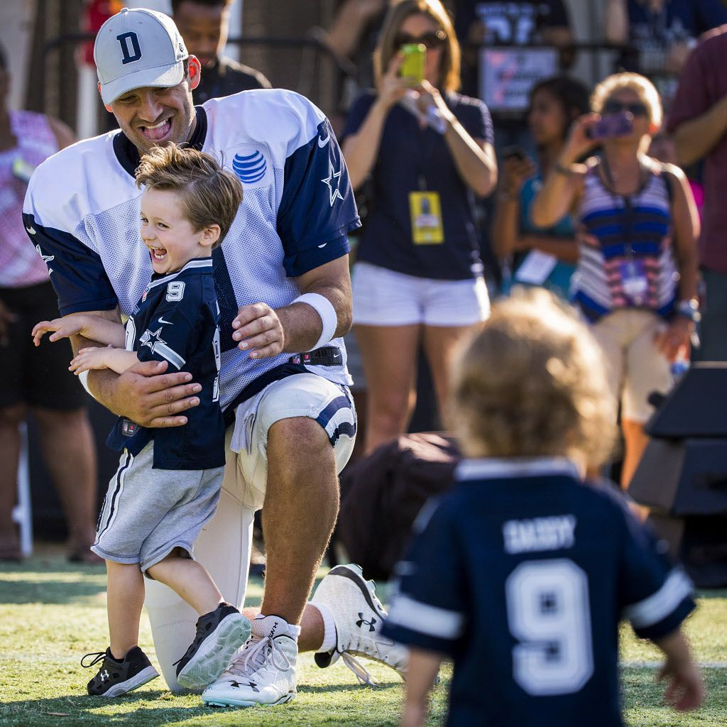 Dallas Cowboys quarterback Tony Romo hugs his son Hawkins, 3, as younger son Rivers, 1, runs to join them as they play on the field after practice at training camp on Saturday, Aug. 15, 2015, in Oxnard, Calif. (Smiley N. Pool/The Dallas Morning News)