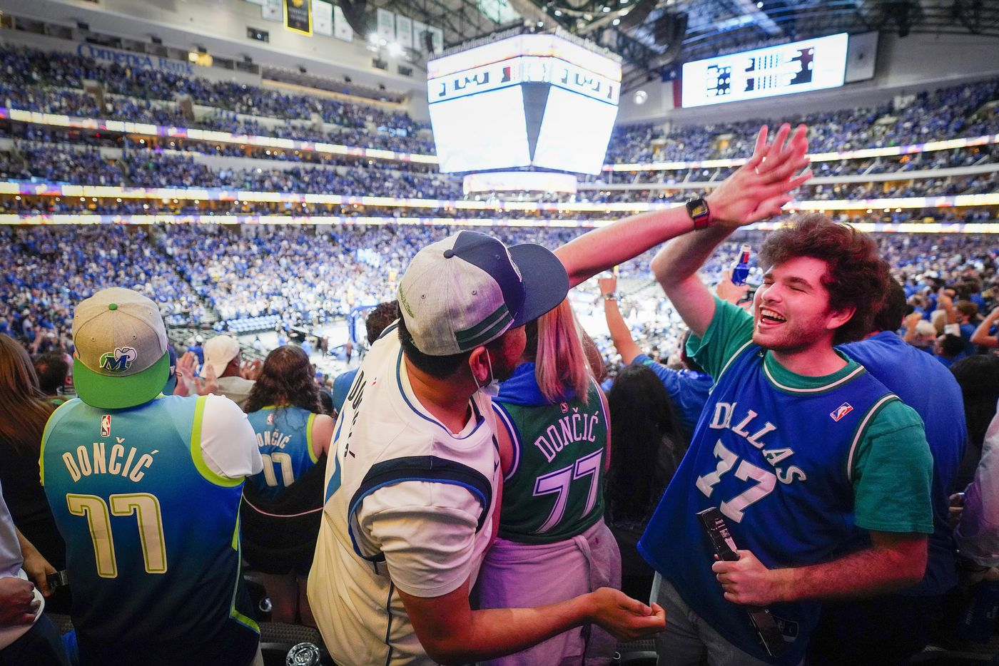 Dallas Mavericks fans Sean Bush (right) and Jay Ramos, all wearing guard Luka Doncic #77 jerseys, cheer a basket during the first quarter of an NBA playoff basketball game against the LA Clippers at American Airlines Center on Friday, May 28, 2021, in Dallas.