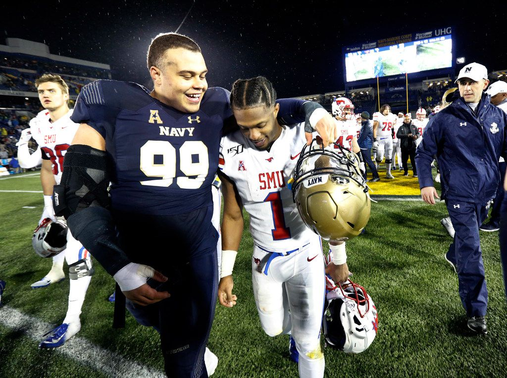 Navy Midshipmen defensive lineman Jackson Pittman (99) walks arm-in-arm with Southern Methodist Mustangs wide receiver CJ Sanders (1) to participate in the Navy Alma Mater following Navy's 35-28 win at Navy-Marine Corps Memorial Stadium in Annapolis, Maryland, Saturday, November 23, 2019. (Tom Fox/The Dallas Morning News)