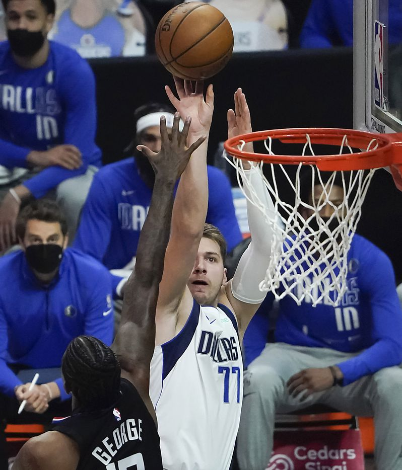 Dallas Mavericks guard Luka Doncic (77) shoots over LA Clippers guard Paul George (13) during the first half of an NBA playoff basketball game at Staples Center on Tuesday, May 25, 2021, in Los Angeles.