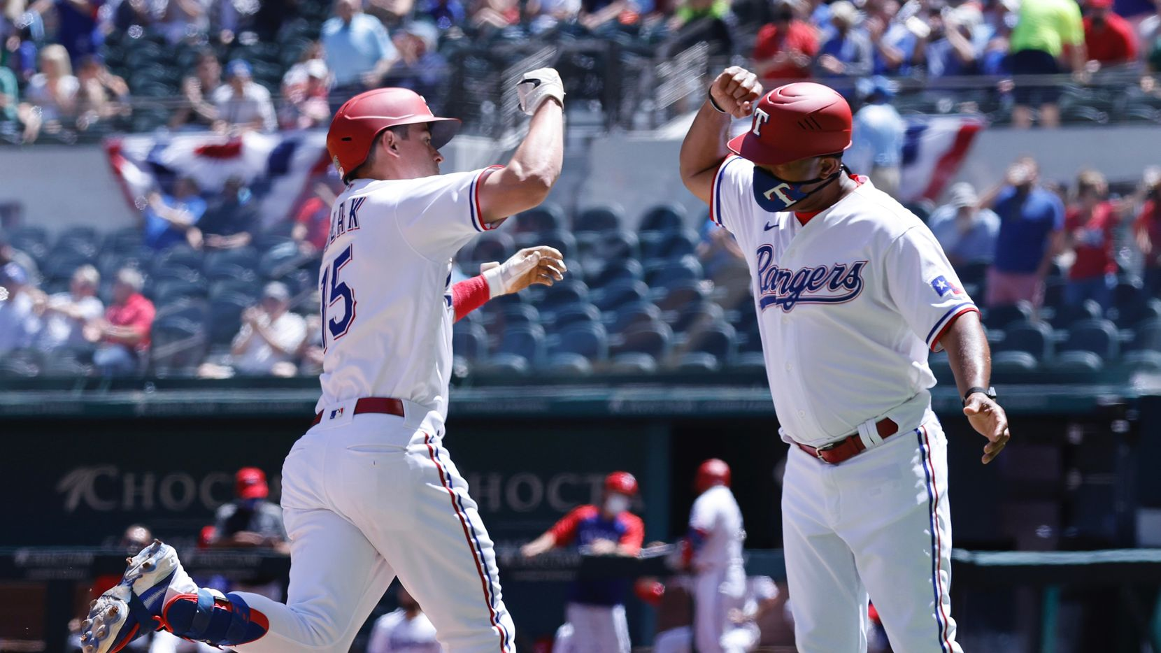 Texas Rangers Nick Solak (15) is congratulated by third base coach Tony Beasley after his second inning solo home run to right field against the Toronto Blue Jays at Globe Life Field in Arlington, Wednesday, April 8, 2021.
