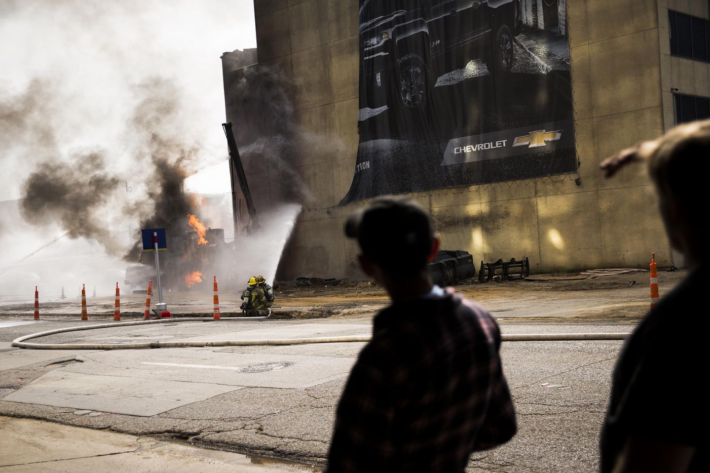 Bystanders watch as Dallas Fire Rescue responds to the scene of a fire at 2100 Main Street where an unspecified company struck a gas line on Friday, March 10, 2017, in Dallas.