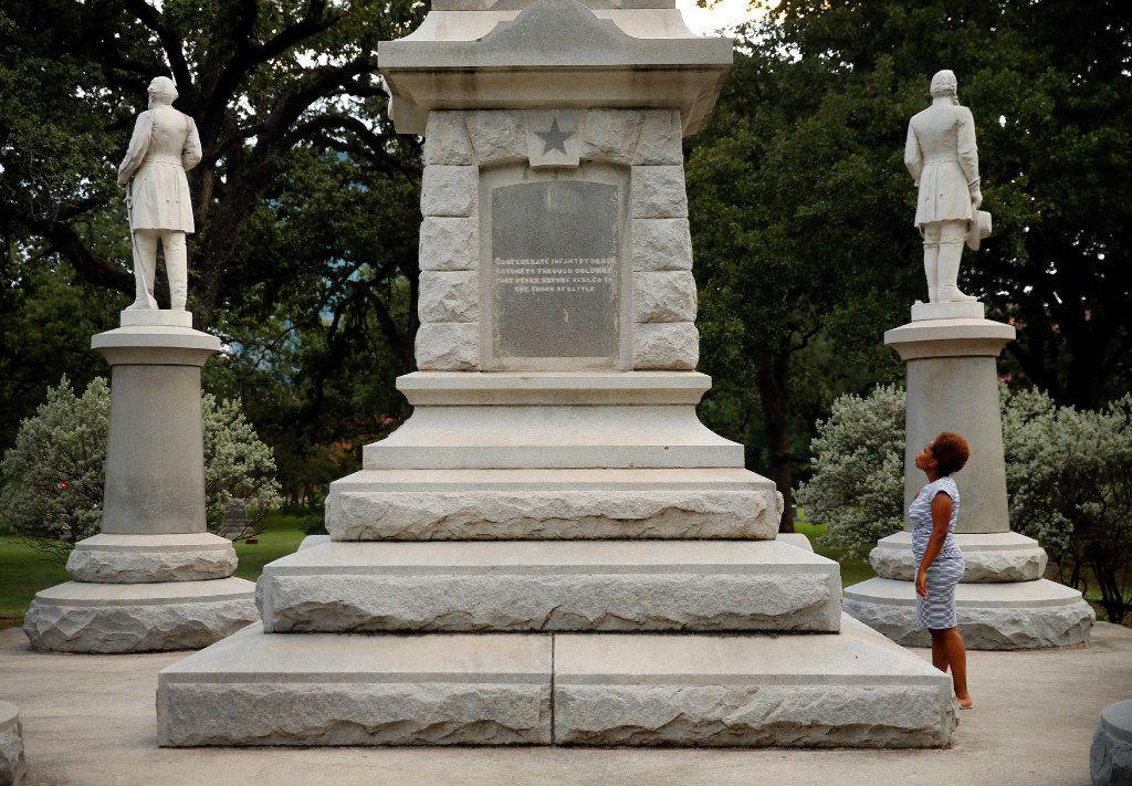Victoria Miller of Dallas reads an inscription on the Confederate War Memorial in Pioneer Park cemetery in downtown Dallas. (File Photo/Tom Fox)