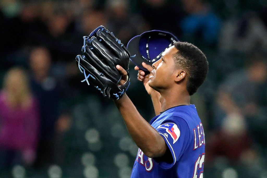 Texas Rangers closing pitcher Jose Leclerc raises his arms skyward after striking out Seattle Mariners' Nelson Cruz to end the baseball game Thursday, Sept. 27, 2018, in Seattle. The Rangers won 2-0. (AP Photo/Elaine Thompson)