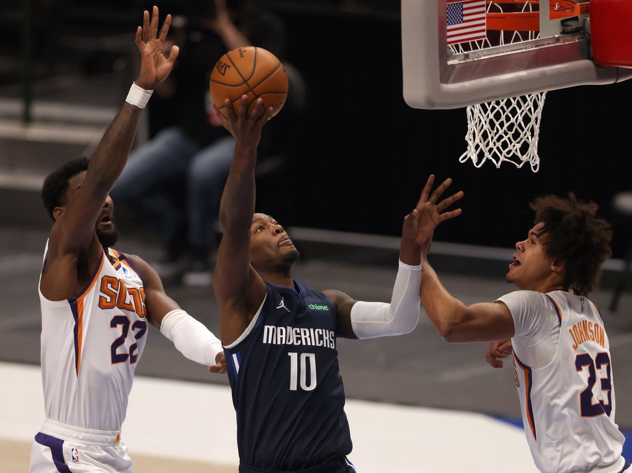 Dallas Mavericks forward Dorian Finney-Smith (10) attempts a shot in between Phoenix Suns center Deandre Ayton (22) and Phoenix Suns forward Cameron Johnson (23) during the first quarter of play at American Airlines Center on Monday, February 1, 2021in Dallas. (Vernon Bryant/The Dallas Morning News)