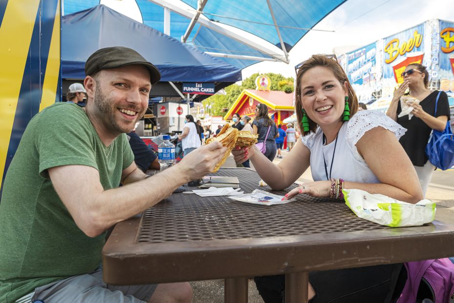 Staff writer Britton Peele, left, and food writer Sarah Blaskovich taste The Armadillo at the State Fair of Texas in 2021. It's so big, there's plenty for each of them when split in half.